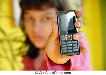 Teen girl showing her mobile phone over yellow