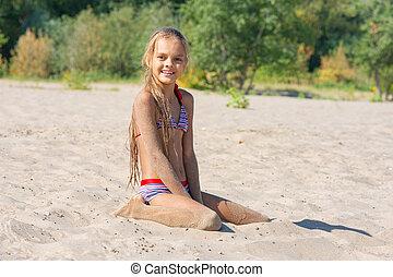 Teen girl sits on a river sandy river beach