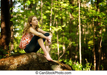 teen girl sitting in a forest daydreaming