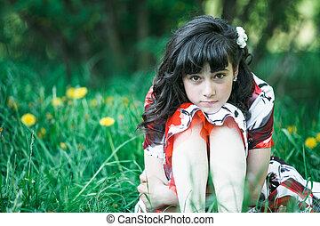 Teen girl sitting in the green grass.