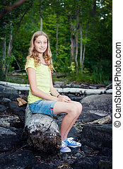 teen girl sitting on a log