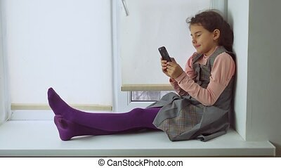 teen girl sitting on a window sill plays the online game for smartphone web