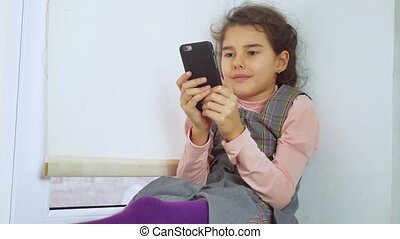 teen girl sitting on a window sill plays web the online game for smartphone