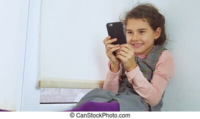 teen girl sitting on a window web sill plays the online game for smartphone