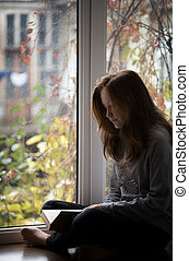 teen girl sitting on a windowsill