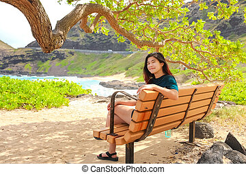 Teen girl sitting on bench under trees by ocean