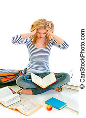 Teen girl sitting on floor among schoolbooks and studying...