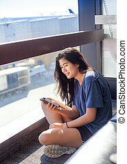 Teen girl sitting on floor at airport looking at smartphone