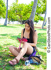Teen girl sitting on grass lawn using smartphone in summer