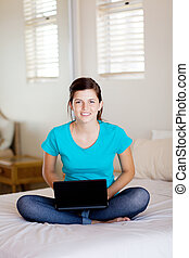 teen girl sitting on her bed and using laptop computer