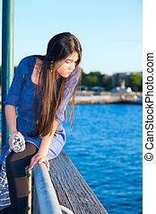 Teen girl sitting on railing overlooking lake