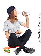 Teen girl sitting on skate board drinking water