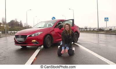 Teen girl sitting on the wet asphalt on the road near the wrecked car. Accident