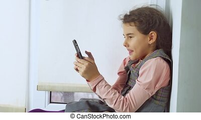 teen girl sitting on web a window sill plays the online game for smartphone