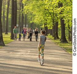 Teen girl skating in park in spring