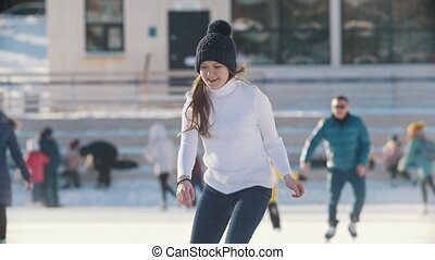 Teen girl skating on outdoor public ice rink, youth pastime...
