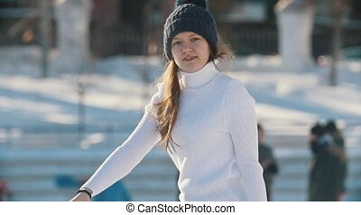 Teen girl skillfully skating on outdoor public ice rink,...
