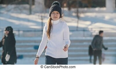 Teen girl skillfully skating on outdoor public ice rink, slow-motion