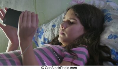 Teen girl smartphone using app on phone lies on bed....
