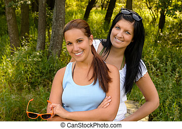 Teen girl smiling with mother in background