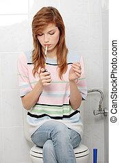 Teen girl smoking in bathroom
