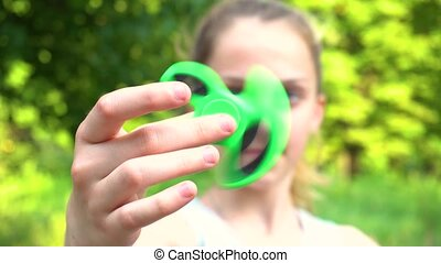 Teen girl spinning spinner in hand - The spinner in teen's...