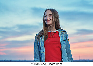 Teen girl standing looking away at sunset background