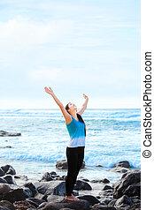 Teen girl standing on rocky beach arms raised, praising God