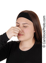 Teen girl standing with eyes and nose closed for stink