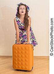 Teen girl standing with suitcase