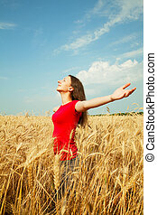 Teen girl staying at a wheat field