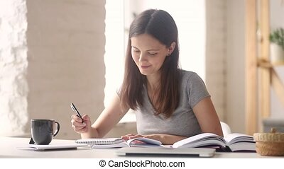 Teen girl student studying making notes in notebook doing research