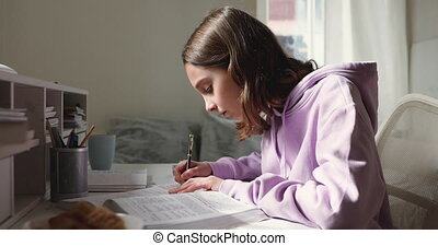 Teen girl studying, reading textbook, making notes at home desk