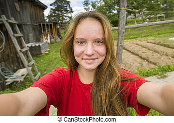 Teen girl taking a selfie outdoors (country house)