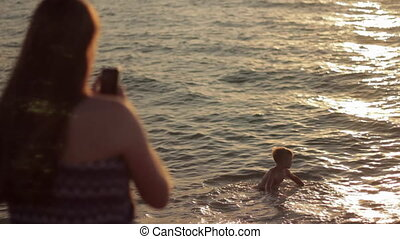 Teen girl Taking Photo little boy with Mobile Smart Phone Camera at Sea Sunset.