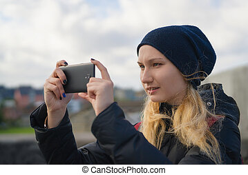teen girl taking photos with smartphone in the city