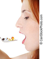 Teen girl taking pills from spoon.