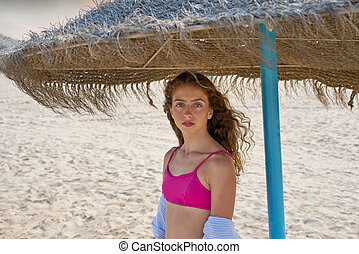teen girl under thatch umbrella on a beach