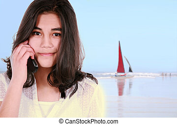 teen girl using cell phone on beach