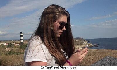 Teen girl using smartphone on the beach.