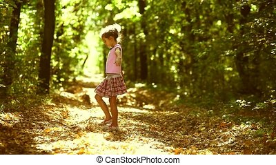 teen girl walking in the forest side playing in the autumn...