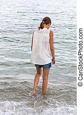 teen girl walks into the sea