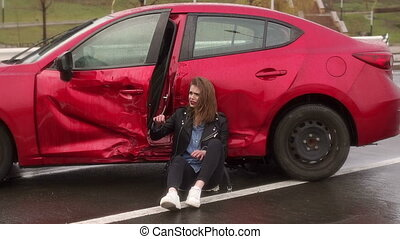 Teen girl was in an accident on the road in the rain, she is injured and scared.