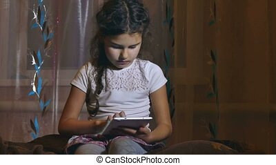 teen girl with a browsing tablet in the room watching online