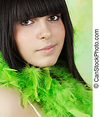 teen girl with a feather boa - closeup portrait of a teen...