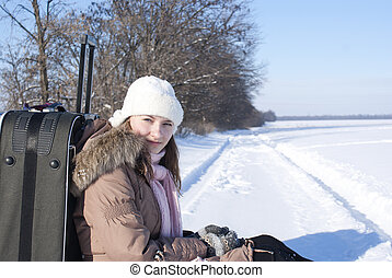 Teen girl with a suitcase outdoors at winter time