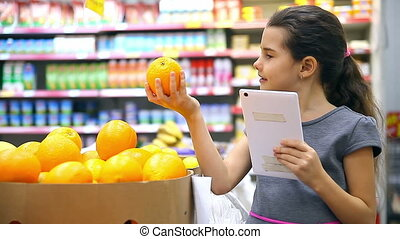 teen girl with a tablet in the supermarket to buy orange