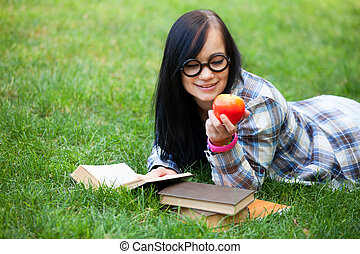 Teen girl with apple in the park.