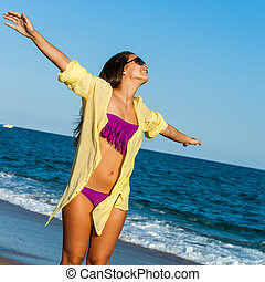 Teen girl with arms open on beach.