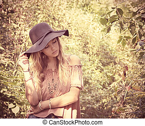 teen girl with black hat in woods